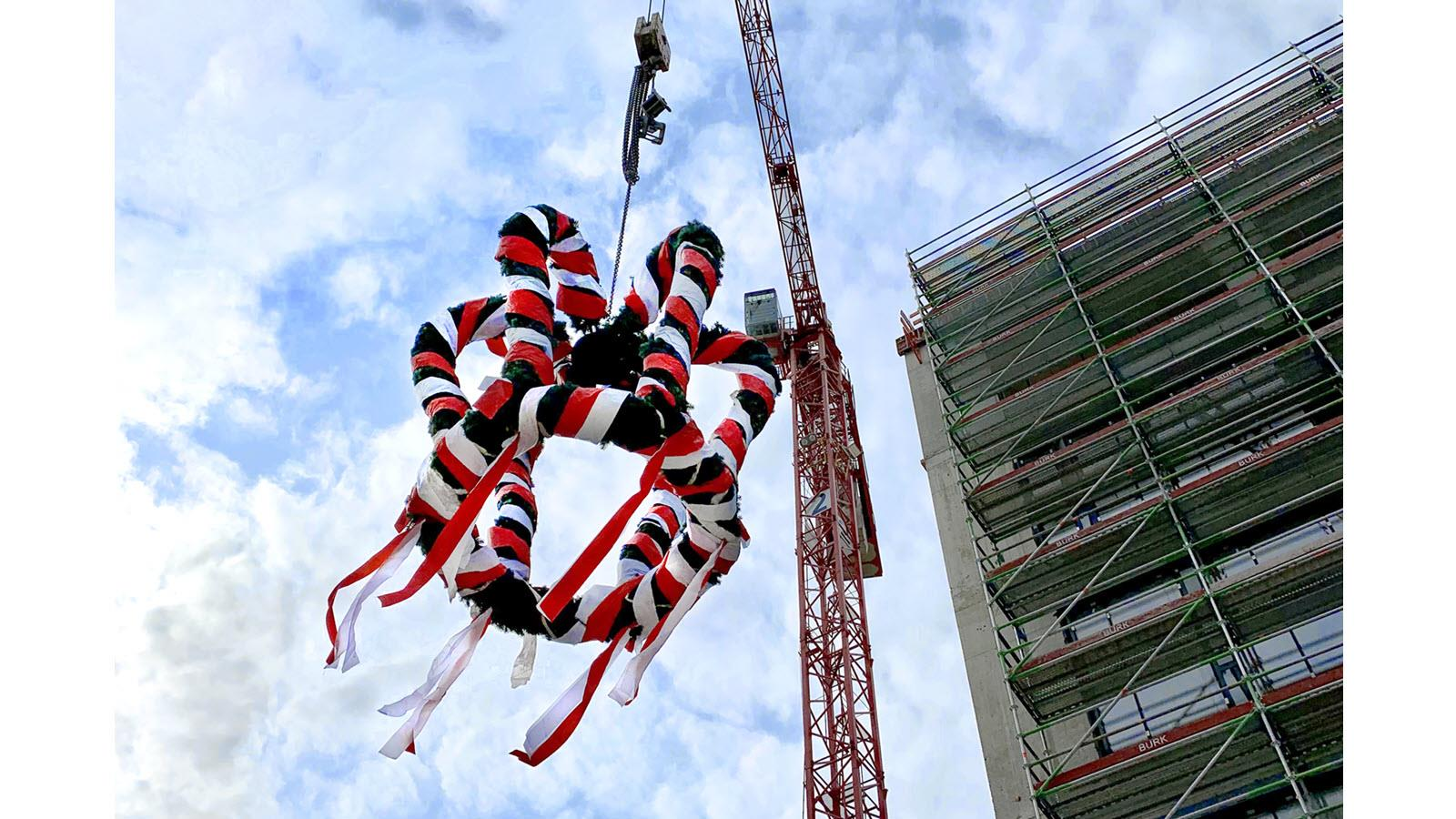 Lifting a wreath of multicolored ribbons to celebrate the topping out of a building in Marburg, Germany