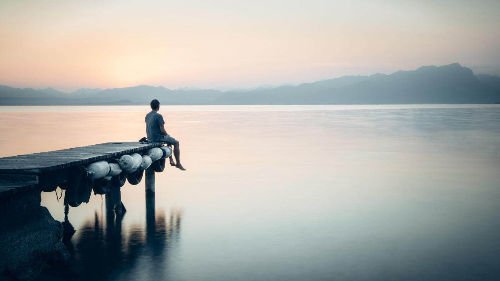 man at the end of a dock on a lake