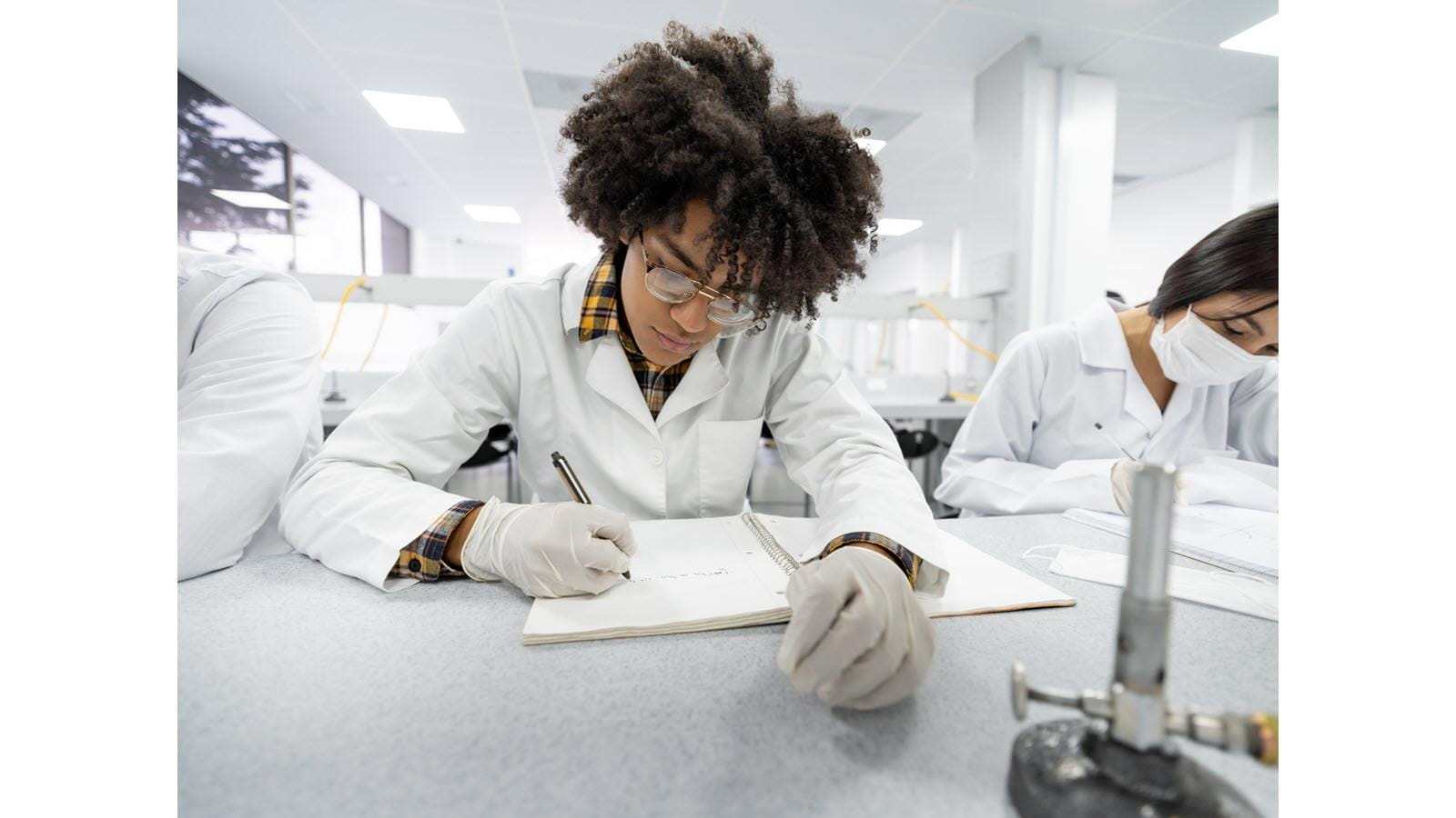 Science student taking notes with gloved hands