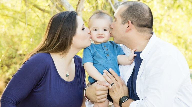 Terry Young and his wife both kiss their infant son on the cheek