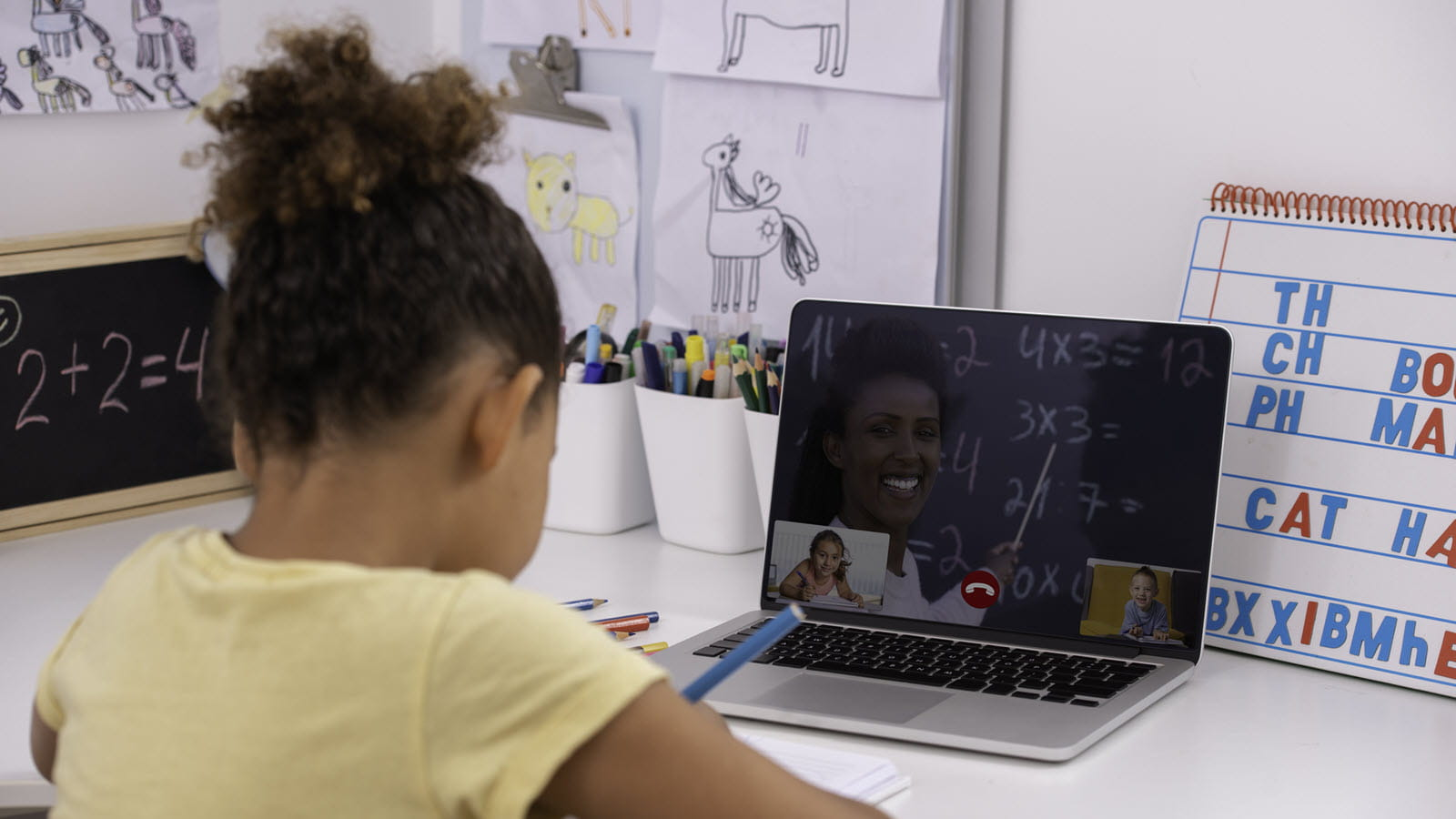 young girl at a home desk with laptop participating in virtual school