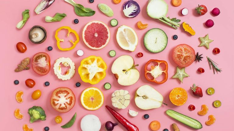 fruits and vegetables on a pink background