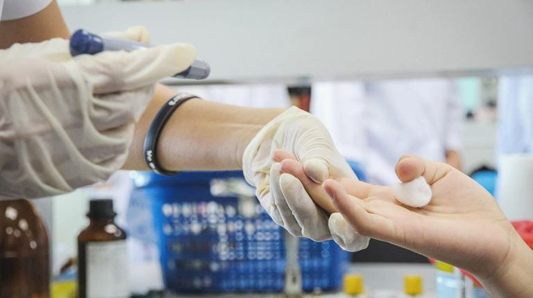 Health care worker takes a patient's hand during a blood test