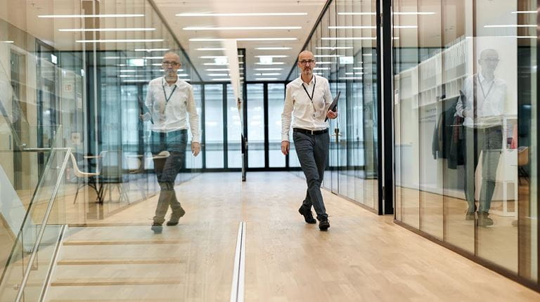 Research Manager Adrian Zuercher walks through sitem-insel his image reflected in glass walls