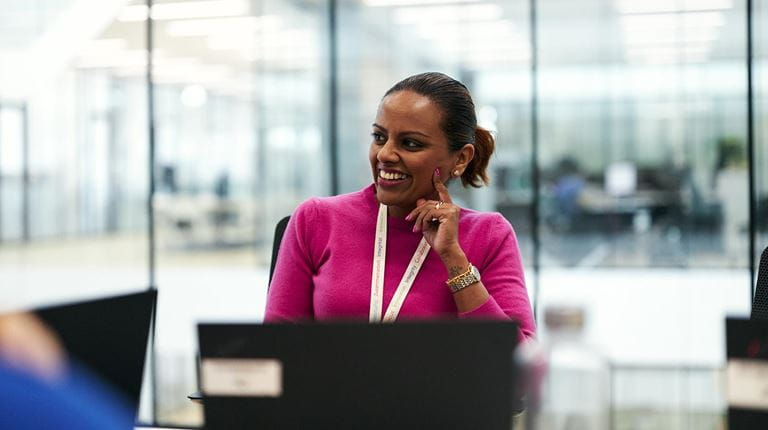 woman in a pink sweater smiles in a meeting